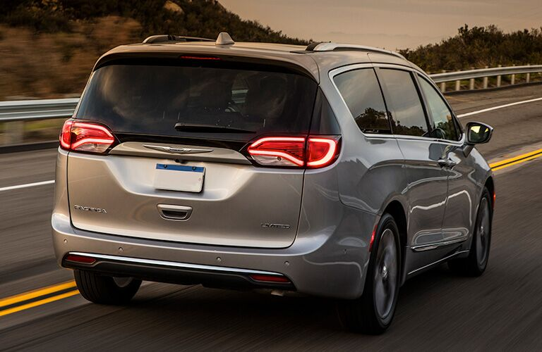 Rear passenger angle of a 2019 Chrysler Pacifica driving on a road