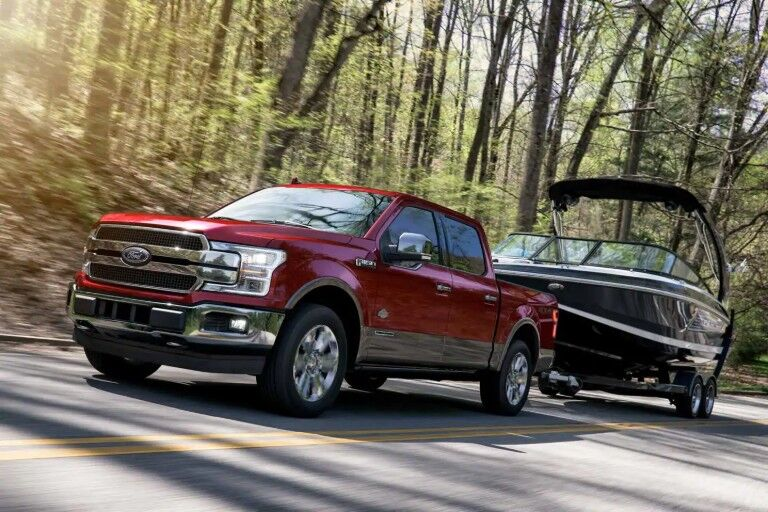 Red 2019 Ford F-150 towing boat down wooded road