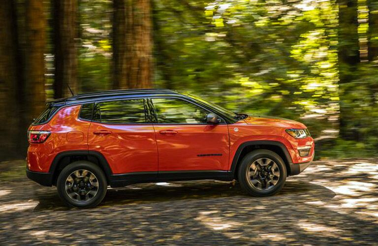 The side view of an orange 2018 Jeep Compass driving in the woods.