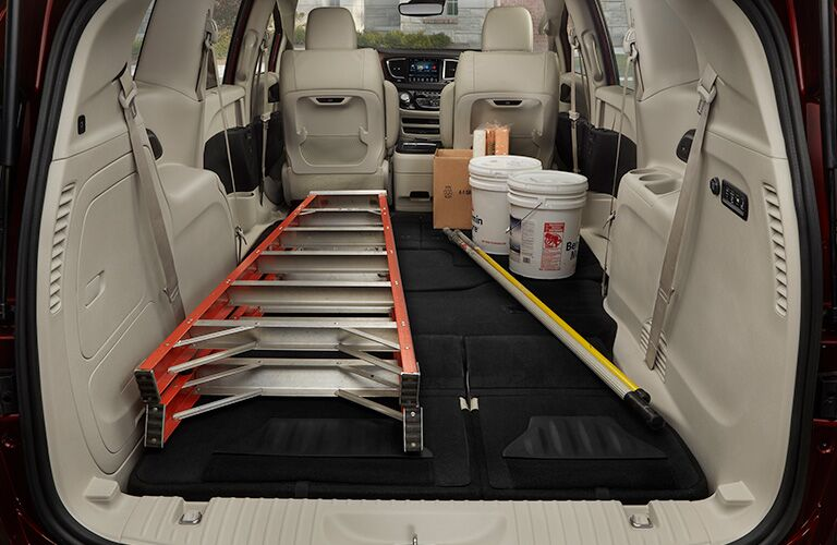 Rear view of the interior of the 2019 Chrysler Pacifica with the seats down and a ladder and painting supplies inside