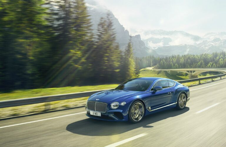 blue Bentley Continental GT on mountain road