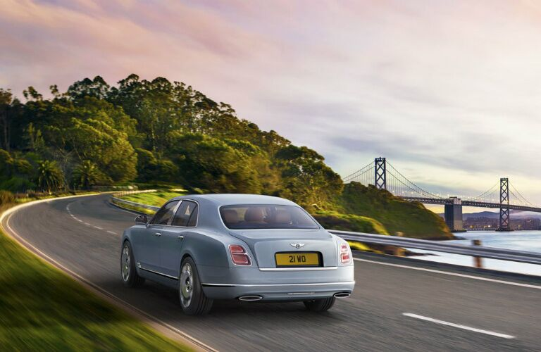 rear view of light blue bentley mulsanne driving toward bridge