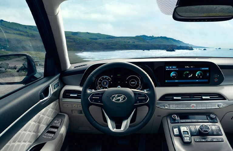 Interior driver area of the 2021 Hyundai Palisade with a body of water and land in view outside the window