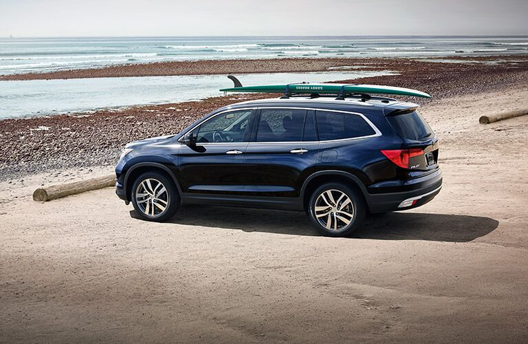 dark blue Honda Pilot parked by beach