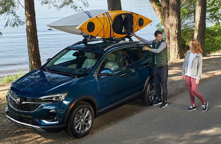 A young couple strapping a set of kayaks to the top of a blue 2021 Buick Encore GX.
