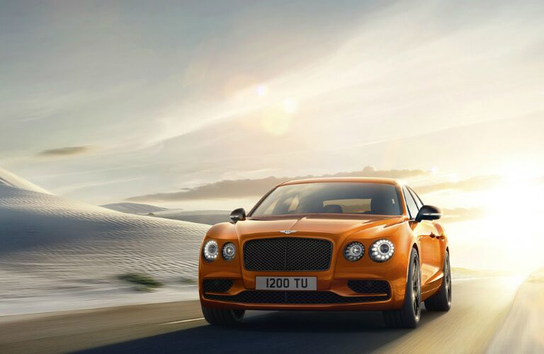 orange bentley flying spur driving in the desert