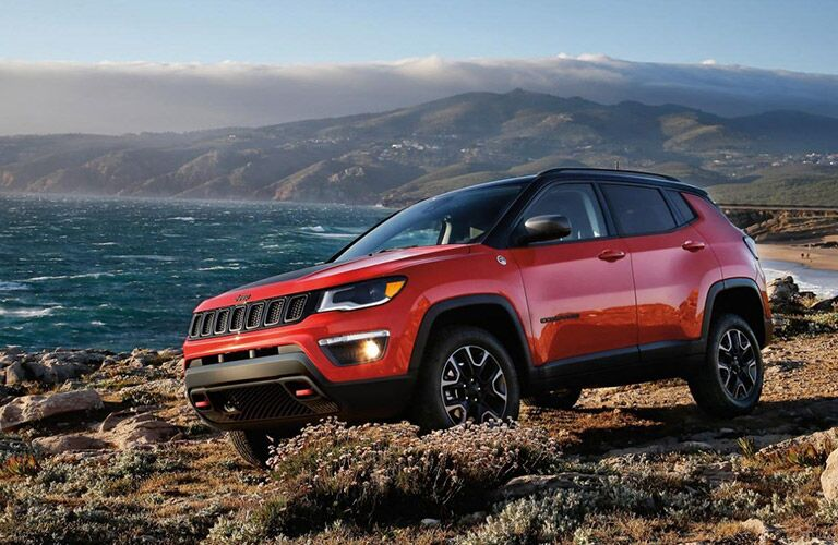 The side view of a red 2020 Jeep Compass driving off-road.