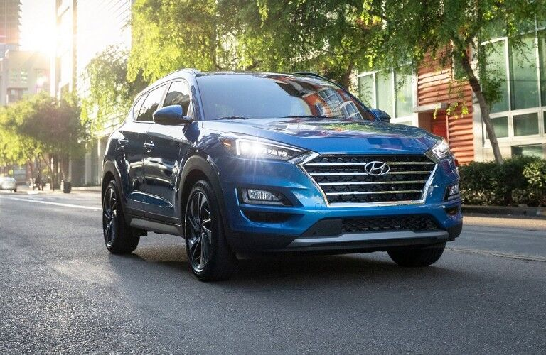 Front and side exterior of a blue-colored 2021 Hyundai Tucson as it drives down a street with its headlights on