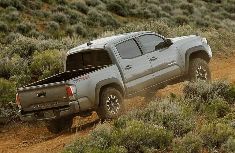 The side and rear view of a silver 2021 Toyota Tacoma driving off-road.