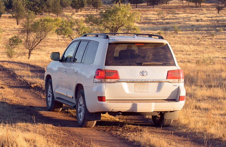 2020 Toyota Land Cruiser driving on dirt road rear view
