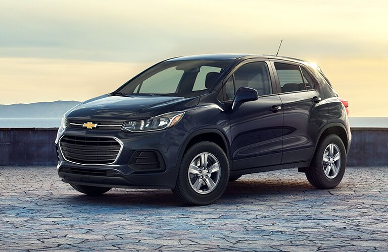 A 2020 Chevrolet Trax parked outside on a stone area with water and large hills in the background