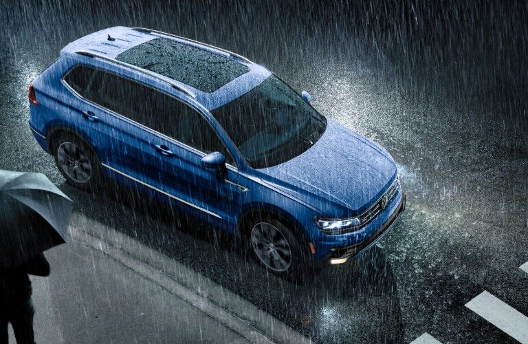 Front passenger aerial angle of a blue 2020 Volkswagen Tiguan driving in the rain