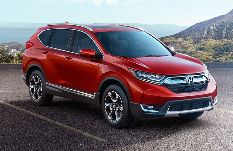 The front and side view of a red 2017 Honda CR-V.
