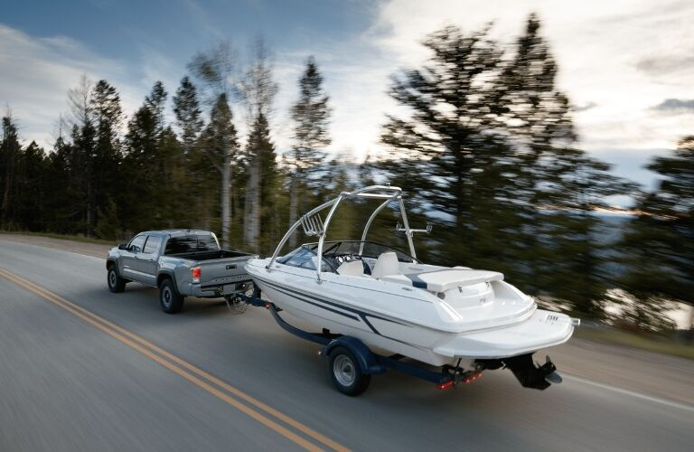 2020 Toyota Tacoma driving away towing a boat