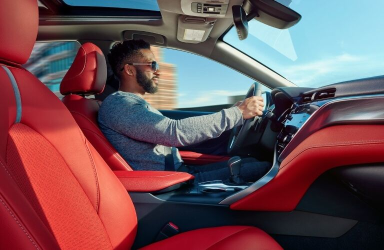Man driving a 2020 Toyota Camry with red interior