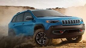 Blue Jeep Cherokee driving in dirt