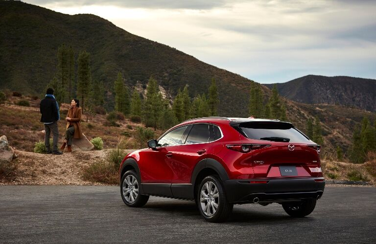 2020 Mazda CX-30 facing a hill with people on top of it