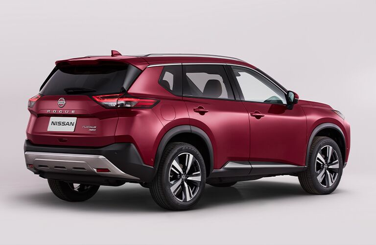 The rear and side view of a red 2021 Nissan Rogue.