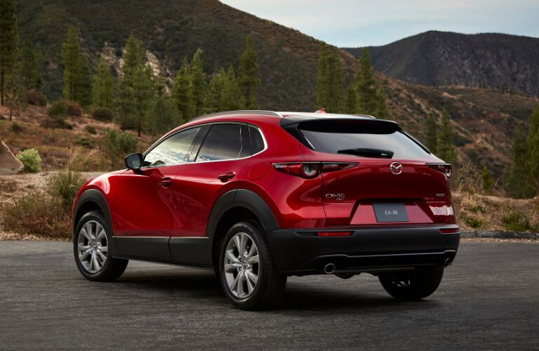The rear and side view of a red 2020 Mazda CX-30 parked near a hilly forest.