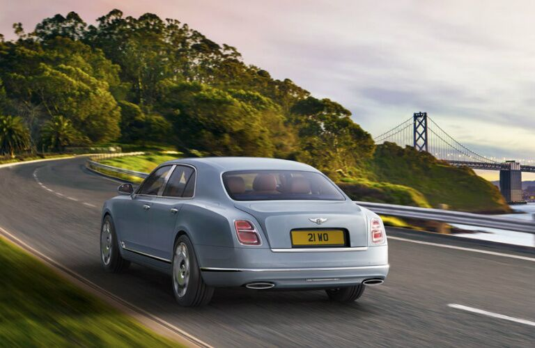 Blue 2020 Bentley Mulsanne driving towards a forest