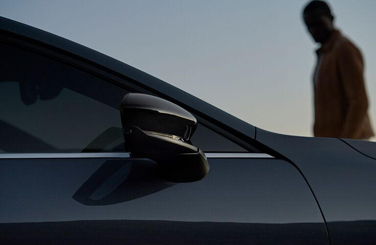 The side view of the passenger-side mirror on a gray 2021 Mazda3 Hatchback.