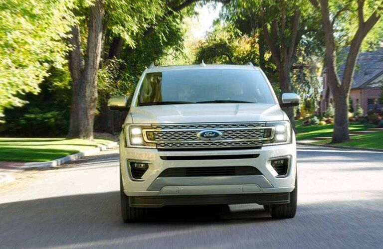 Front view of white 2019 Ford Expedition driving through residential area