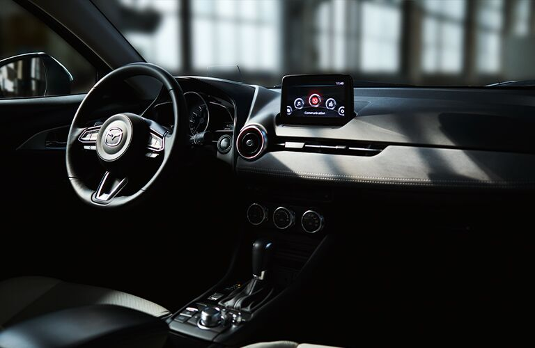 The front interior image of the steering wheel and center console inside a 2020 Mazda CX-3.