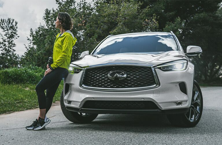 woman leaning on the 2020 Infiniti QX50