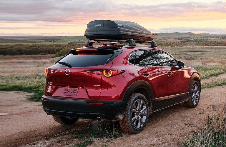 The rear and side view of a red 2021 Mazda CX-30 driving off-road with a roof rack.