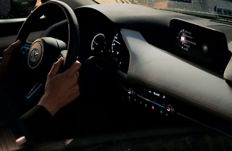 A close photo of human hands on a steering wheel inside the 2021 Mazda3 Sedan