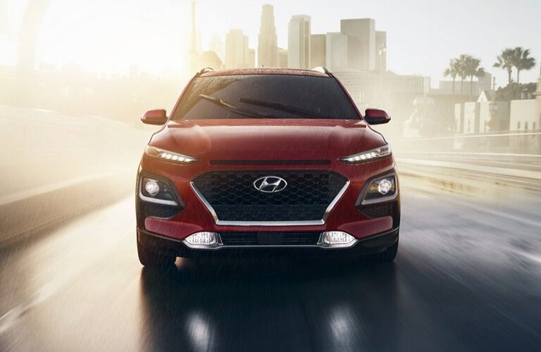 Red 2021 Hyundai Kona driving on road away from a city