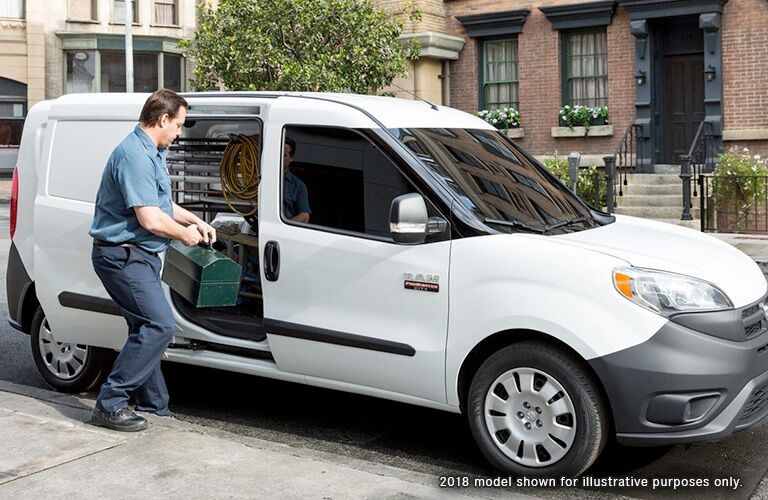 "Front passenger angle of a white 2019 RAM ProMaster City with a man putting supplies inside and the text ""2018 model shown for illustrative purposes only"""