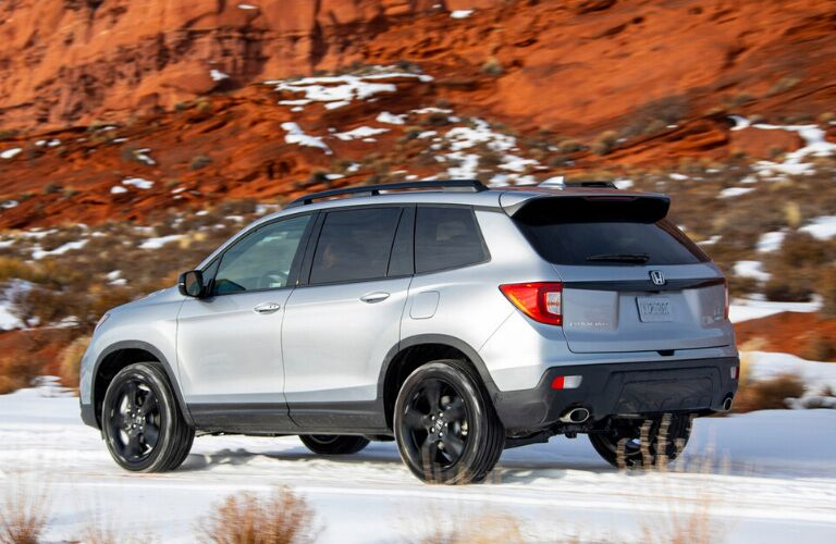 Rear view of silver 2020 Honda Passport on snowy terrain
