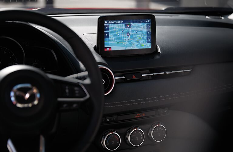 Interior view of the steering wheel and touchscreen display with navigation inside a 2020 Mazda CX-3
