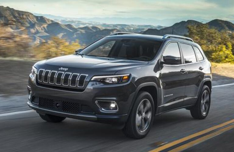 The front view of a black 2020 Jeep Cherokee driving down the open road.