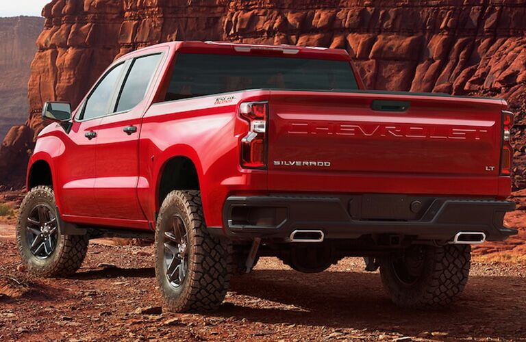 Rear driver angle of a red 2019 Chevrolet Silverado parked outdoors in a rocky environment