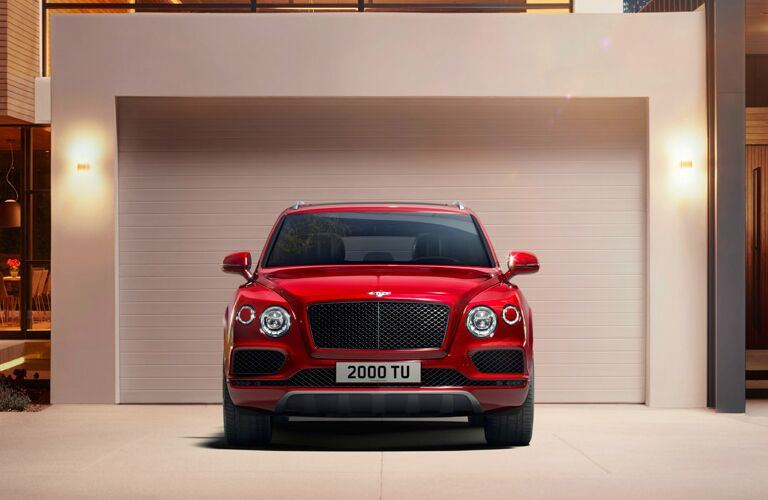 Red 2020 Bentley Bentayga parked in front of a garage