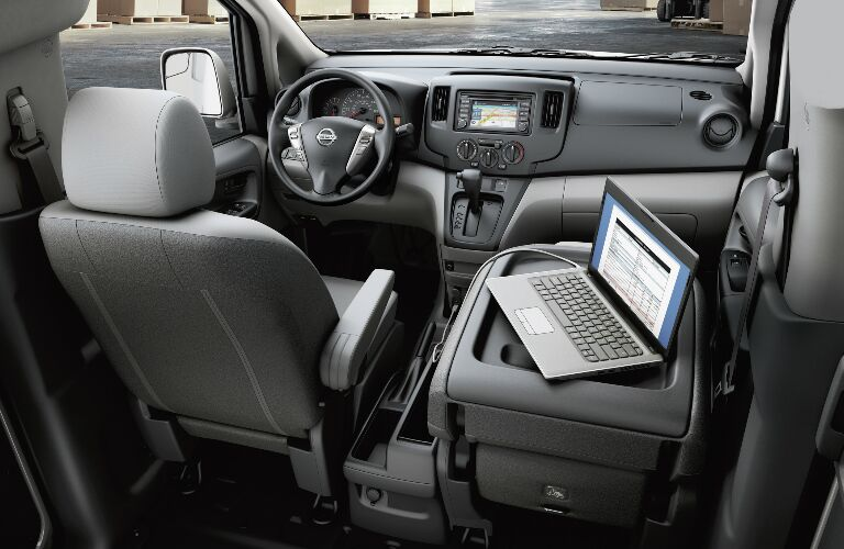 A laptop on a folded-down passenger's seat in a 2019 Nissan NV200 Compact Cargo Van