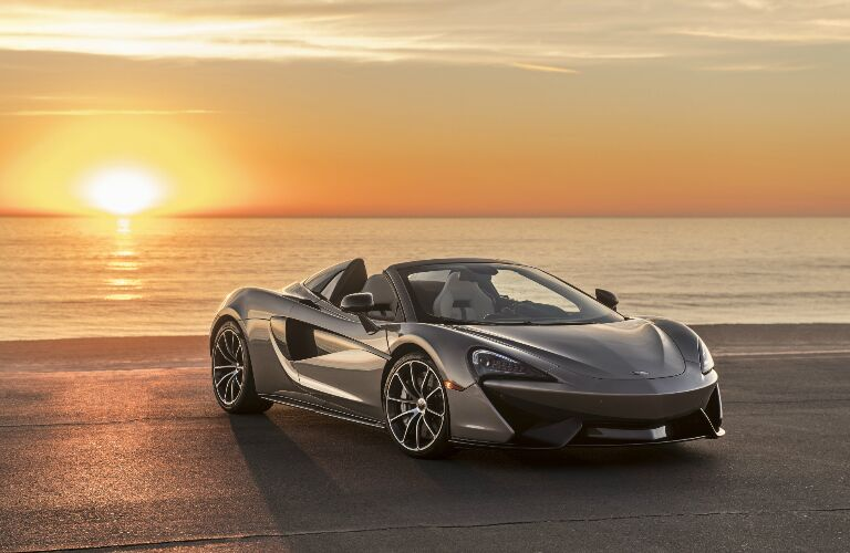 Grey 2019 McLaren 570S Spider with the sun setting over the ocean
