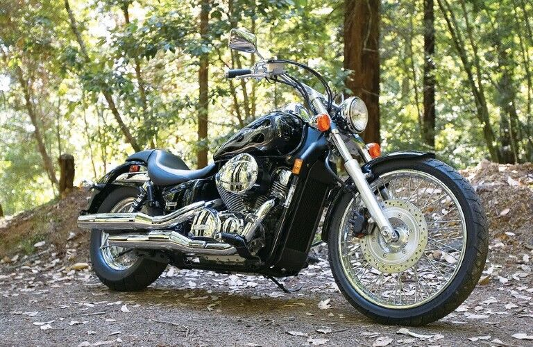 A black Honda Shadow Spirit 750C2 parked in a wooded area.