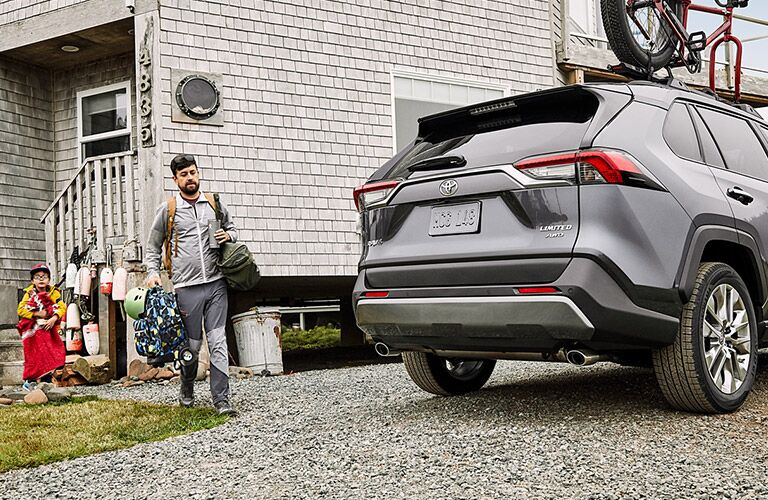 Rear view of 2020 Toyota RAV4 parked next to father and child carrying bags