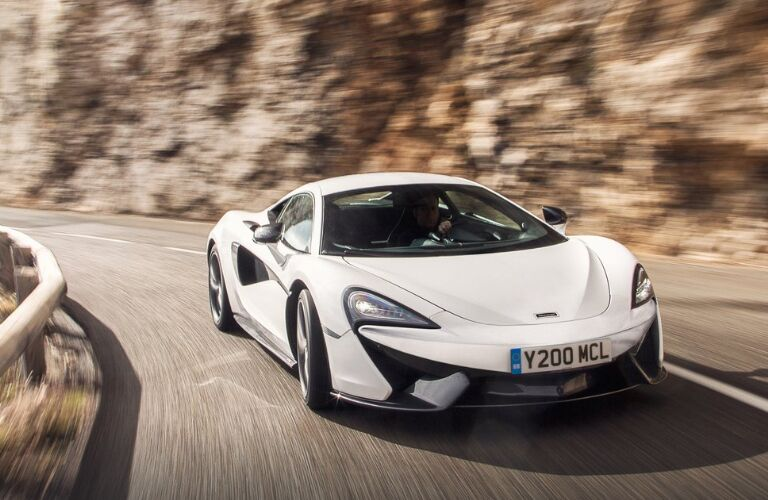 White 2019 McLaren 570S driving on a mountain road
