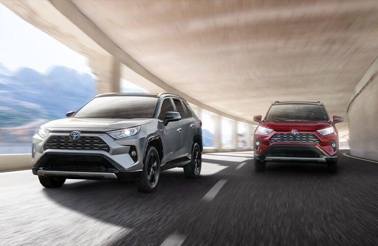 A gray and a red 2021 Toyota RAV4 Hybrid driving down a road next to each other.