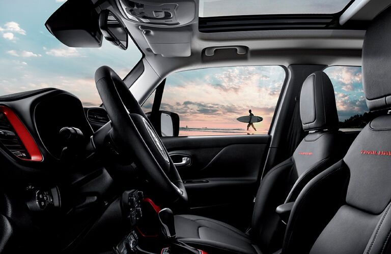 Front row of 2021 Jeep Renegade with surfer and body of water in background