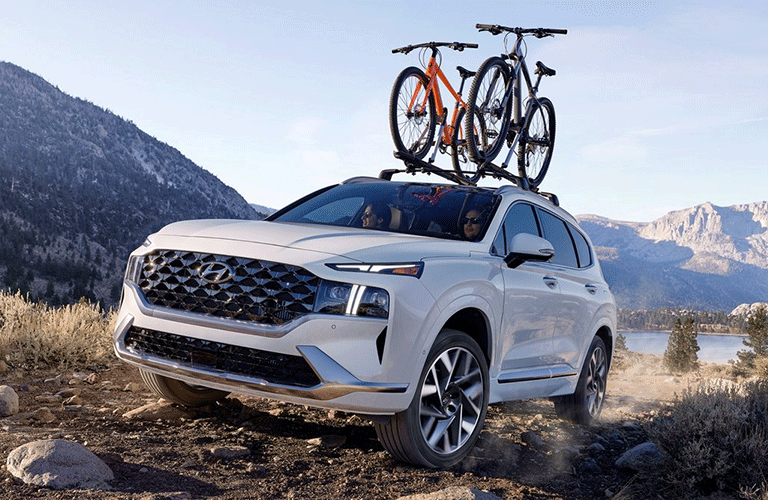 A white-colored 2021 Hyundai Santa FE with two bikes strapped to the roof of the vehicle.