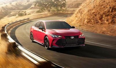 red 2021 Toyota Avalon going around curve