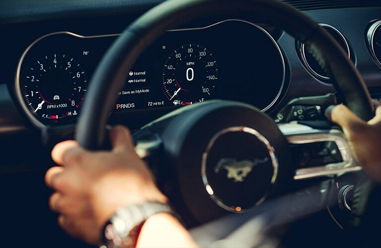 Hands gripping steering wheel of 2019 Ford Mustang