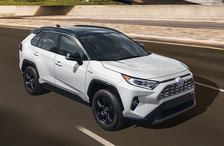 The top and side view of a white 2021 Toyota RAV4 Hybrid.