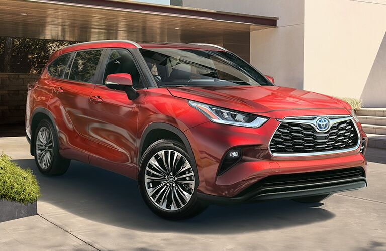 The front and side view of a red 2020 Toyota Highlander Hybrid.