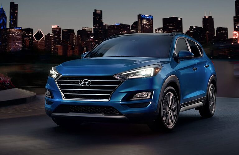 Front view of blue 2020 Hyundai Tucson with city background